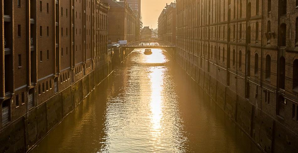 Die untergehende Sonne spiegelt sich in einem Kanal der Hamburger Speicherstadt