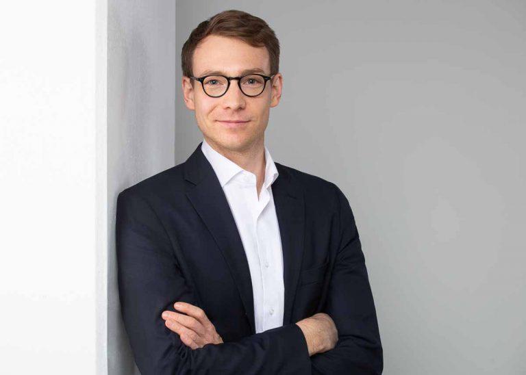 Bewerbungsfotos Berlin -Modernes Bewerbungsfoto eines Mannes, der in einem dunkelblauen Sakko und weißem Hemd vor einem hellgrauen Hintergrund an einer Säule lehnt vom Fotostudio Farbtonwerk in Berlin Mitte