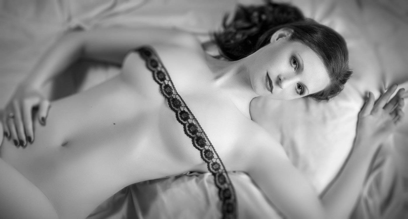 Schwarzweiss Aktfoto einer Frau die auf dem Rücken auf einem Bettlaken liegt und deren Brüste von einer Spitzenbordüre bedeckt sind.