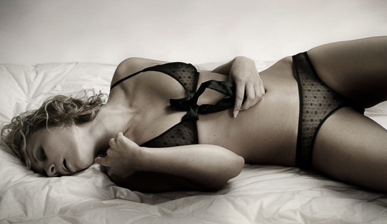 Erotik Foto einer Frau in schwarzer Unterwäsche, die auf dem Rücken in einem Bett liegt