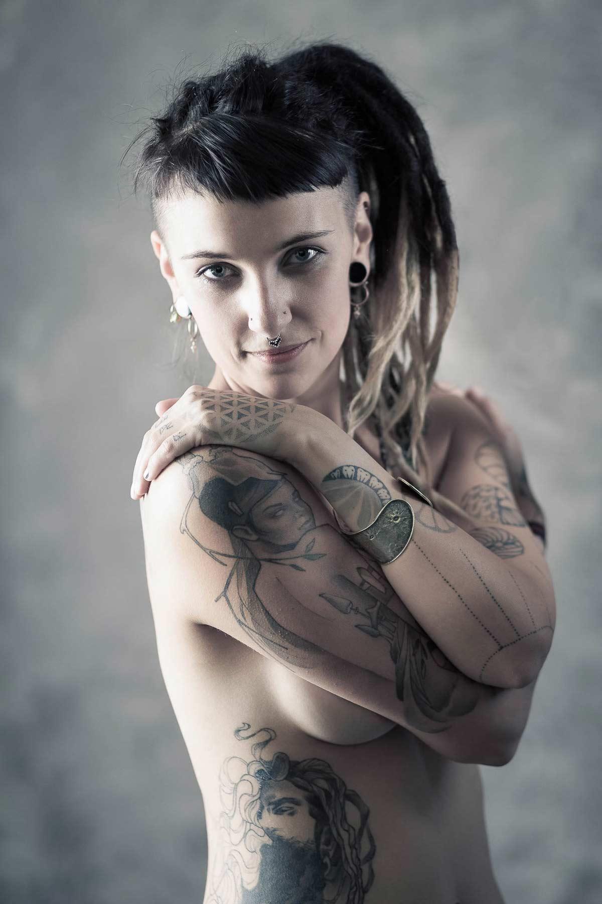 Portraitfoto einer Frau mit Dreadlocks und einem Nasenpiercing