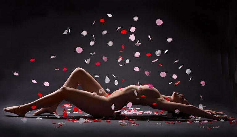 Aktfoto einer Frau die auf dem Rücken liegt und auf die Rosenblütenblätter fallen vor schwarzem Hintergrund