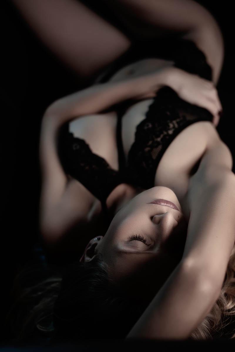 Eine junge Frau in schwarzer Unterwäsche liegt verträumt, sinnlich auf dem Rücken.