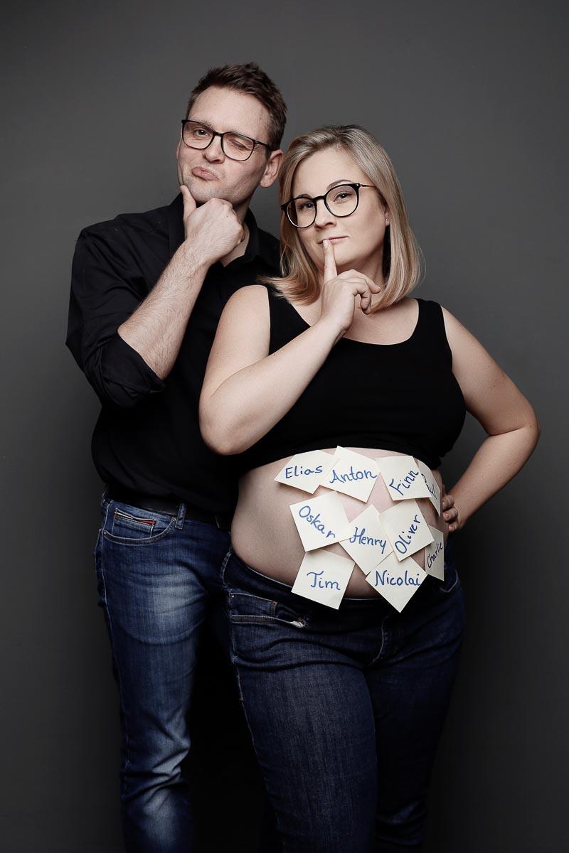 Werdende Eltern, überlegen, welchen Namen das Kind bekommen soll. Die Namen sind auf Post-Its geschrieben, die auf den Babybauch der Mutter kleben