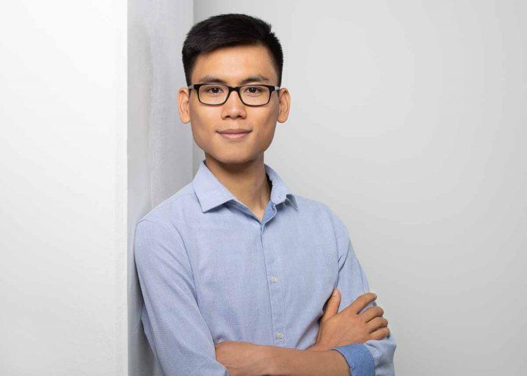 Bewerbungsfotos Berlin -Modernes Bewerbungsfoto eines asiatischen jungen Mannes, mit Brille und blauem Hemd. der locker an einer Säule lehnt vor einem hellen Hintergrund vom Fotostudio Farbtonwerk in Berlin Mitte