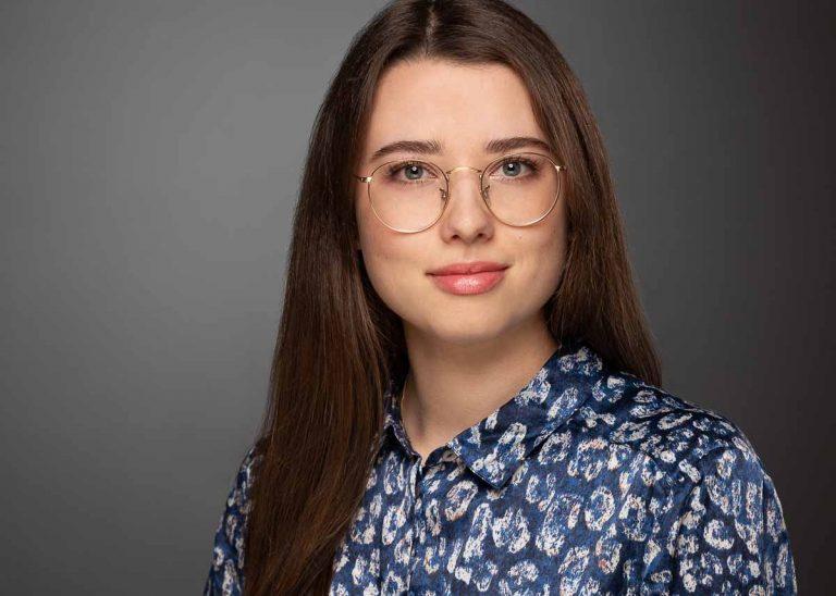 Modernes Bewerbungsfoto einer jungen Frau mit dunkelbraunen, langen Haaren und einer großen Brille, die eine Bluse mit blauem Muster trägt