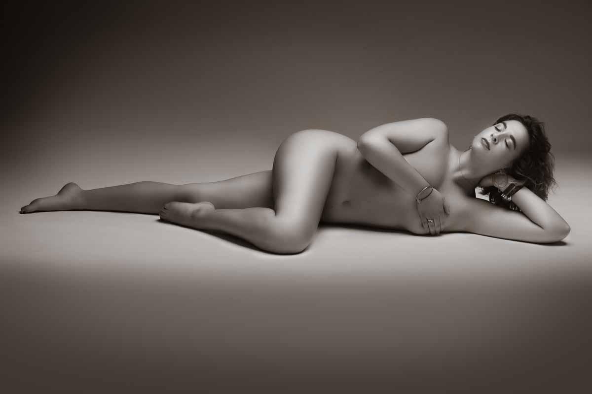 Schwarzweiss Aktfoto einer jungen kräftigen Frau, die seitlich auf dem Boden liegt.