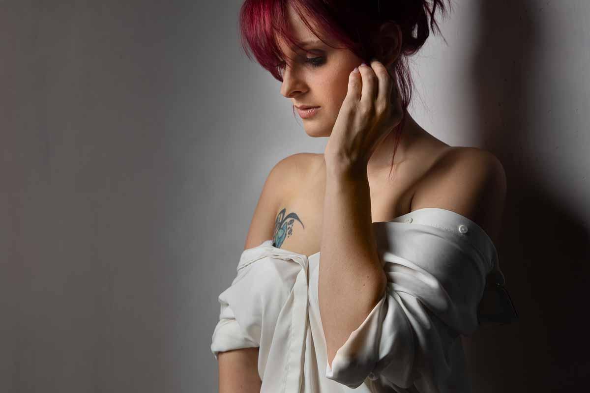 Erotisches Foto einer rothaarigen Frau mit einer Tätowierung über der Brust lehnt an einer Wand