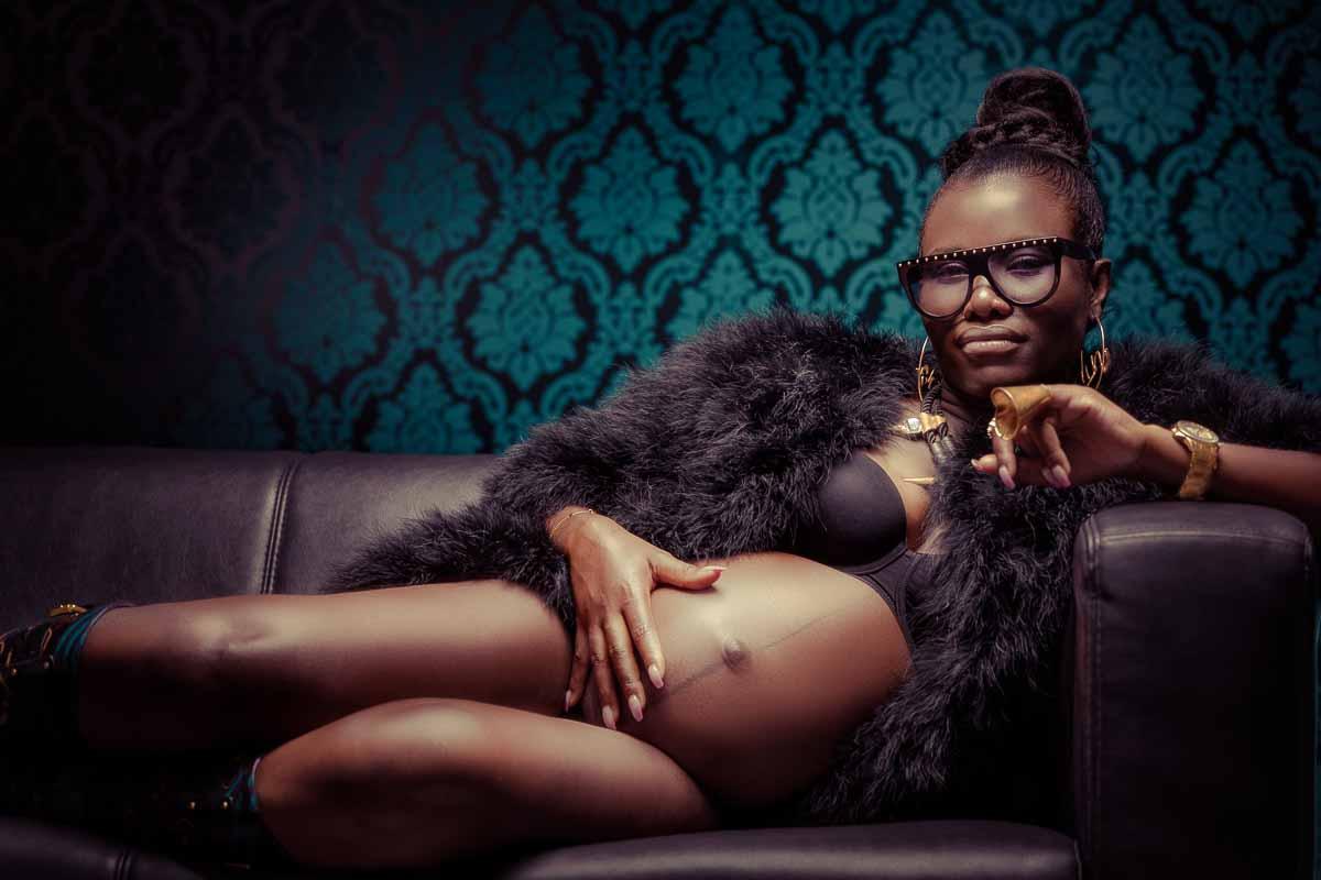 Fotoshooting einer schwangeren dunkelhäutigen Frau, die im Gangster Ghetto-Style auf einer schwarzen Ledercouch liegt