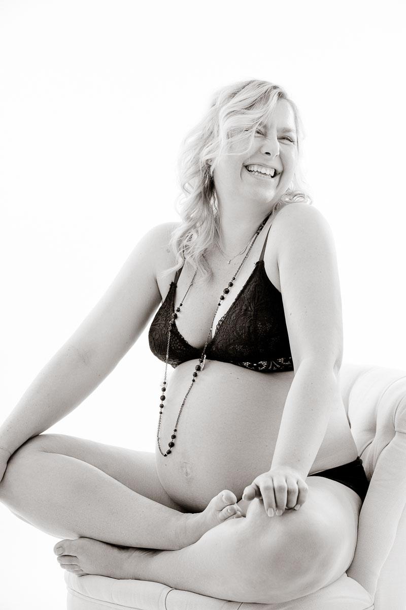 Fotoshooting einer glücklich lachenden schwangeren Frau die in schwarzer Unterwäsche in einem Sessel sitzt.