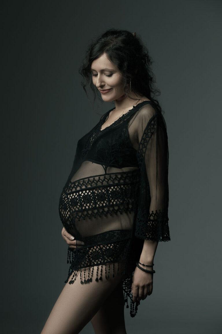 Babybauchfoto einer Frau mit schwarzen Haaren in einem schwarzen Negligee, die glücklich auf ihren Babybauch blickt