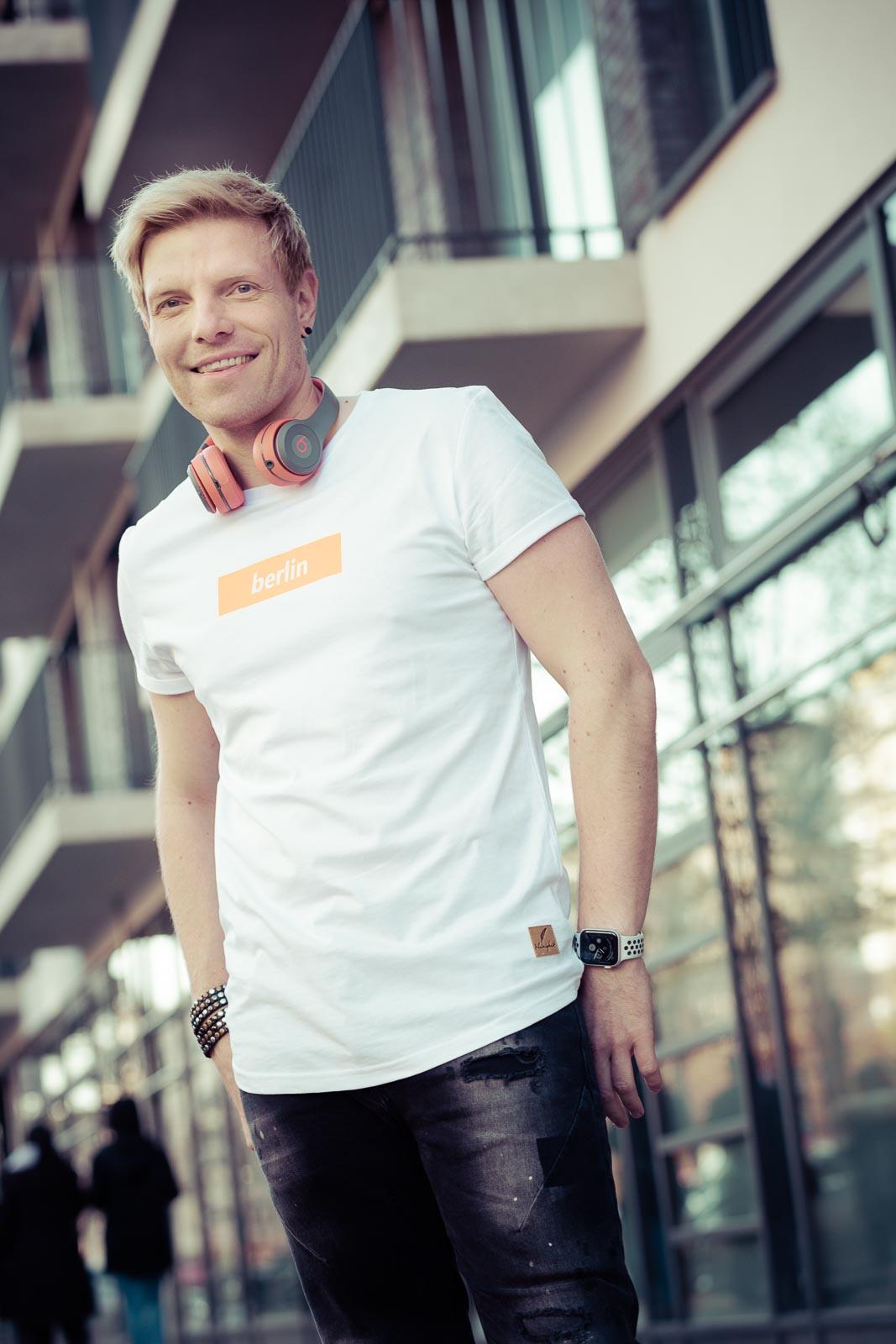 Dating-Foto eines jungen blonden Mannes in weißem T-Shirt und Beats-Kopfhörern vor einer moderene Hausfassade
