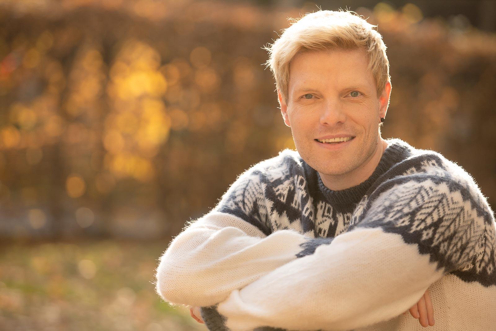 Dating-Foto eines lächelnden jungen blonden Mannes in einem warmen, hellen Strickpullover vor herbstlichem Hintergrund