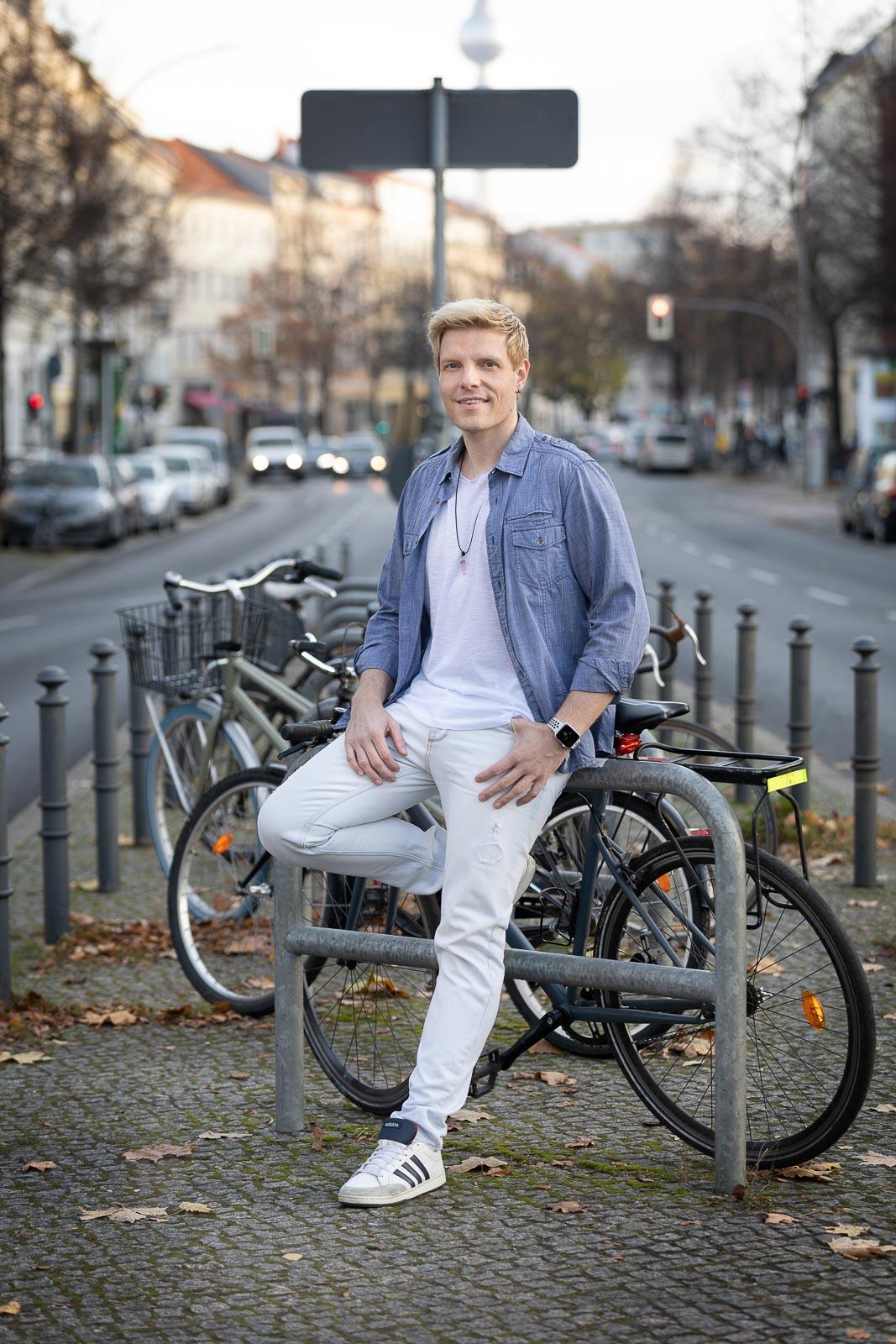 Dating-Foto eines lächelden jungen blonden Mannes in einem Jeanshemd, der in der Stadt lässig an einem Fahrrad lehnt