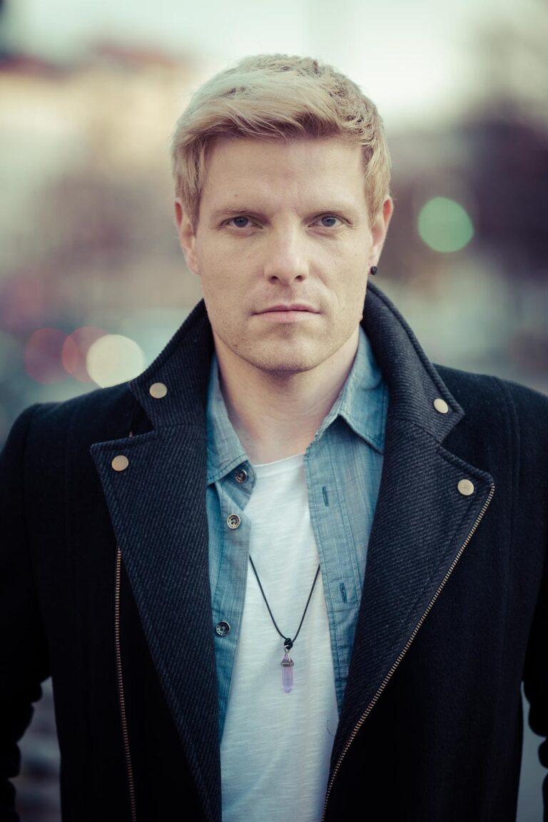 Dating-Foto eines ernst blickenden jungen blonden Mannes der einen dunklen Mantel mit hochgeschlagenem Kragen über einem Jeanshemd trägt.