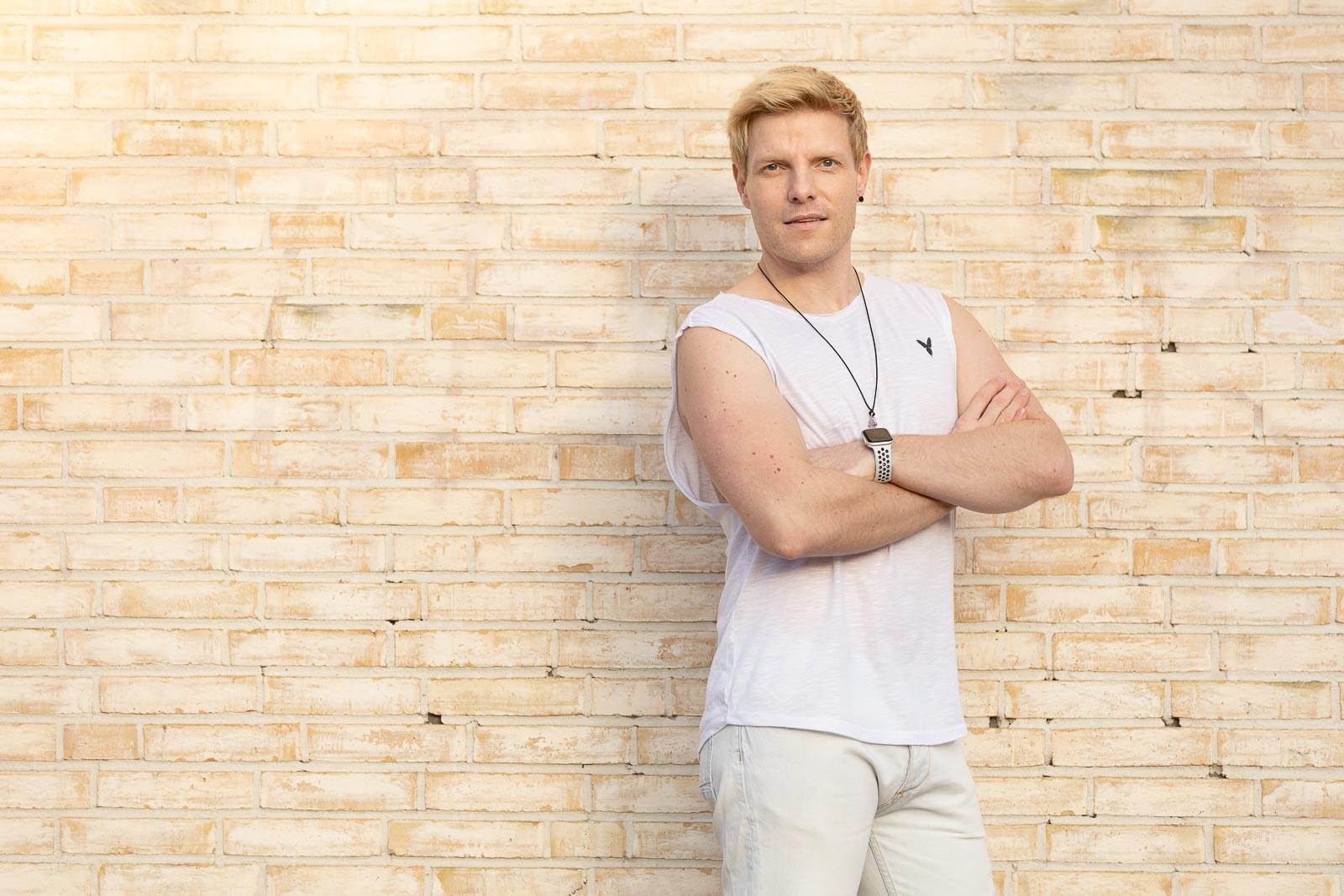 Dating-Foto eines jungen blonden Mannes in weißem T-Shirt, der lässig an eine gelbe Klinkermauer lehnt
