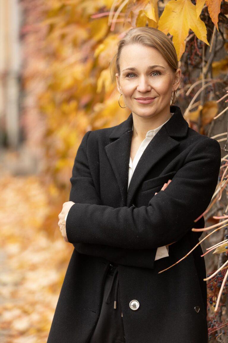 Dating-Foto einer freundlich lächelnden Frau, die mit verschränkten Armen vor Herbstlaub steht