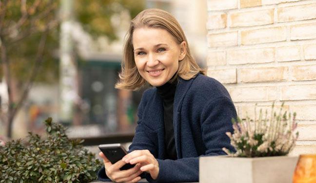 Dating-Foto einer blonden jungen Frau mit schulterlangen Haaren, die mit ihrem Handy in der Hand am Tisch eines Straßenkaffees sitz