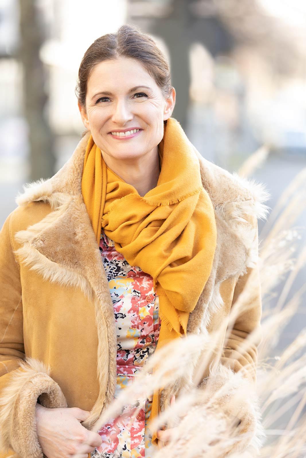 Dating-Foto einer sympathischen braunharigen Frau mit hellbraunem Ledermantel und gelbem Schal