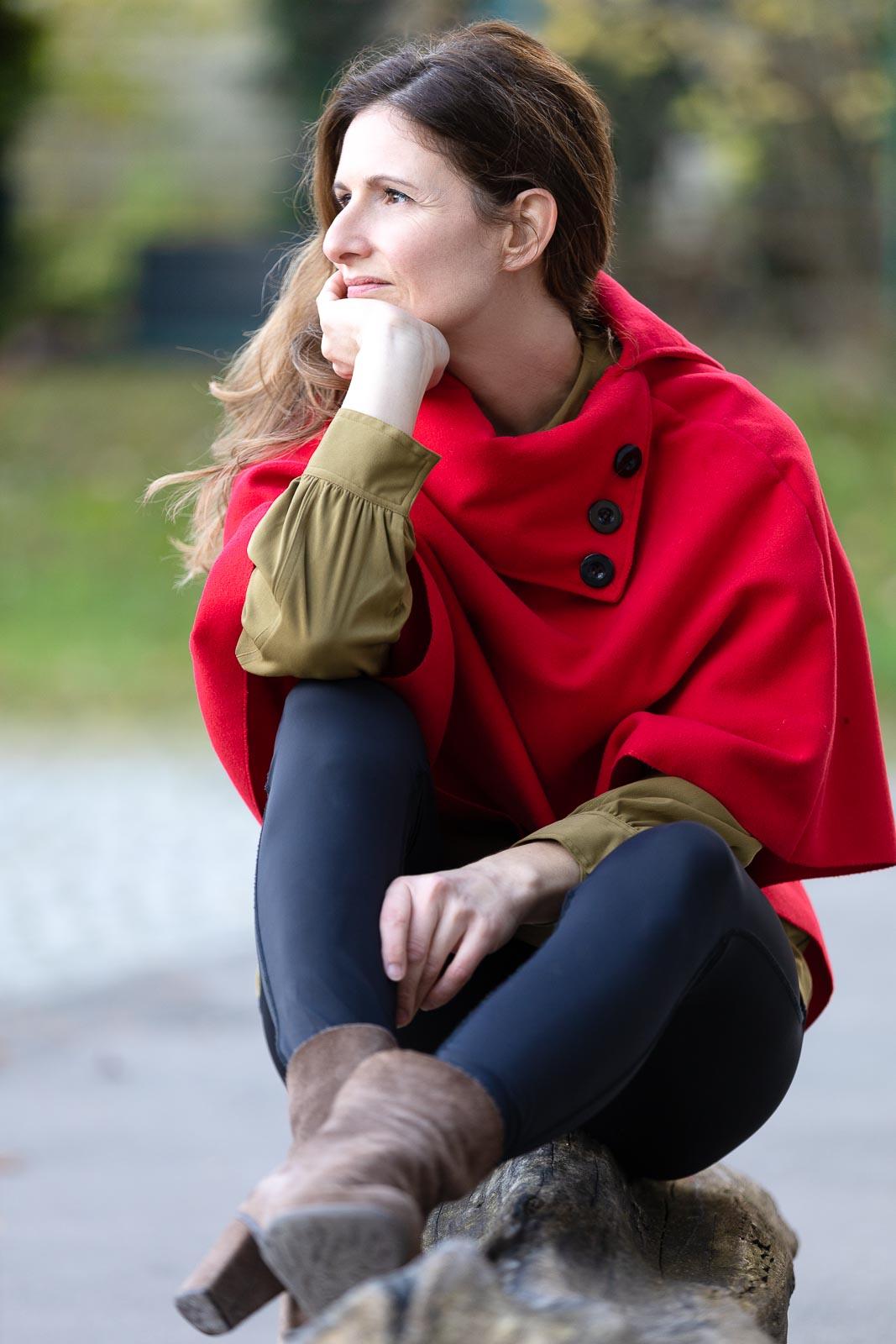 Dating-Foto einer braunhaarigen Frau mit rotem Mantel die nachdenklich auf einem Baumstamm sitzt