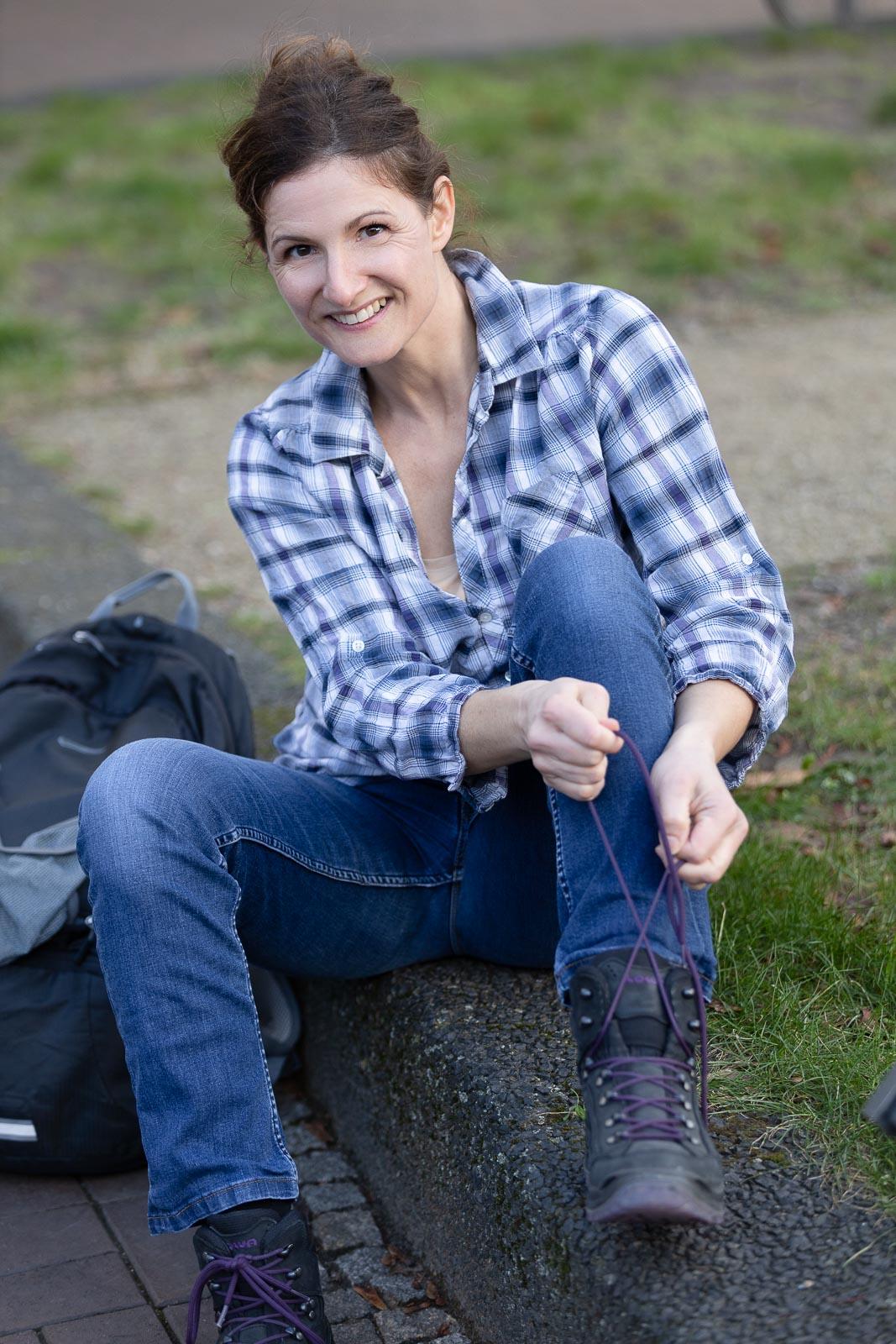 Dating-Foto einer lachenden, braunhaarigen Frau in blau karriertem Hemd die ihre Wanderstiefel zubindet