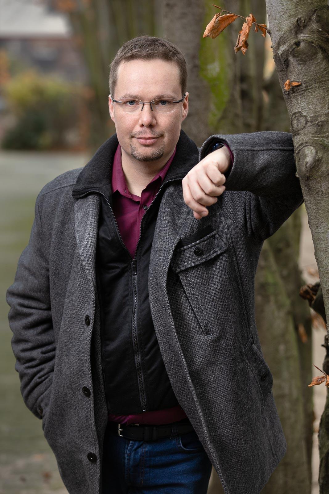 Dating-Foto eines jungen Mannes in einer warmen Jacke, der souverän an einem Baum lehnt