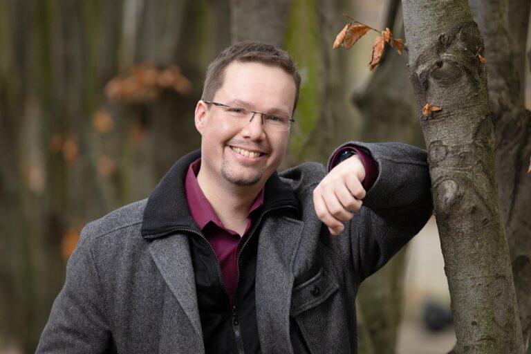 Dating-Foto eines jungen Mannes in einer warmen Jacke, der sich freundlich lächelnd an einem Baum lehnt