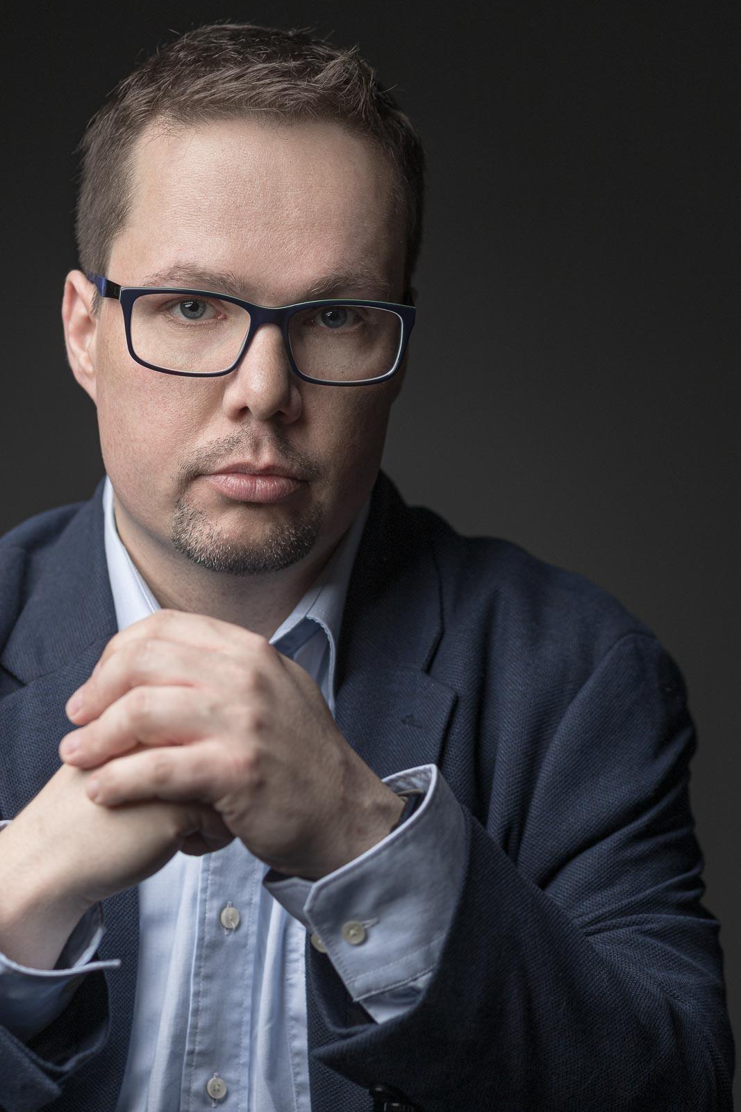 Dating-Foto eines jungen Mannes in blauem Sakko und moderner Brille, der entschlossen in die Kamera blickt