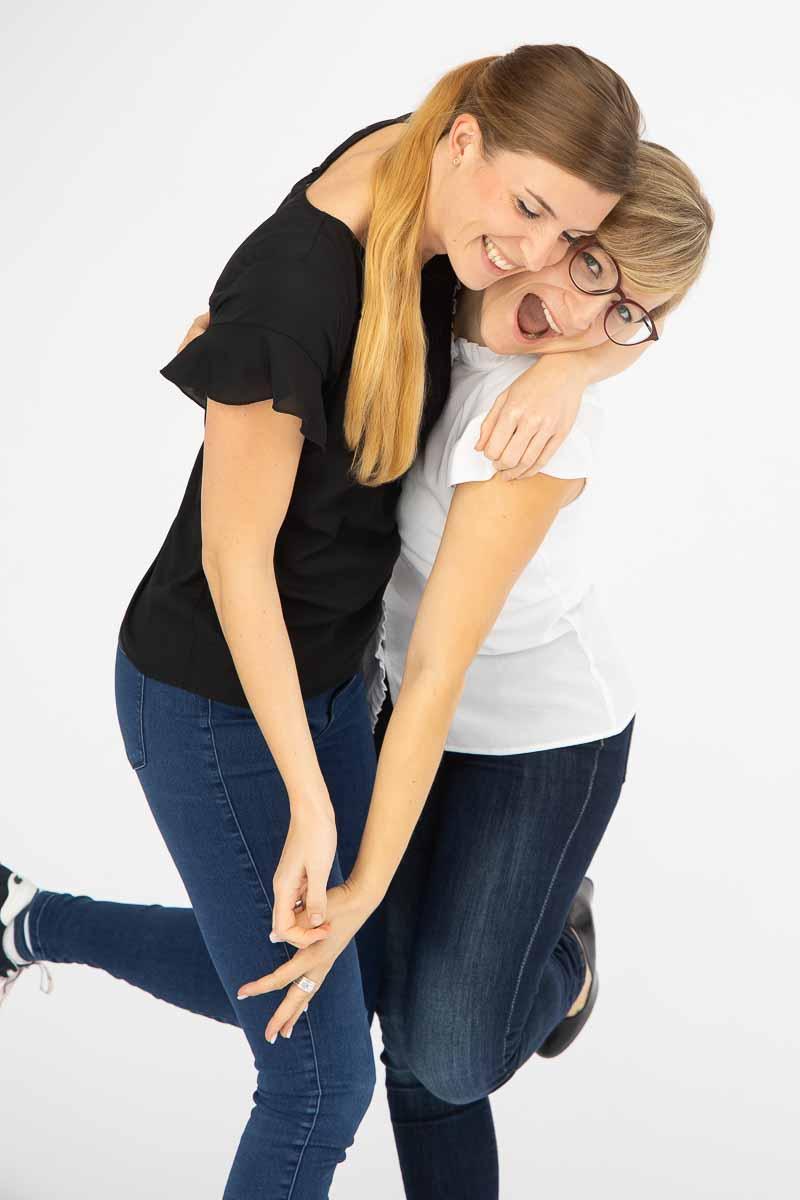 Zwei junge Frauen, die vergnügt vor weißem Hintergrund zusammen Tanzen