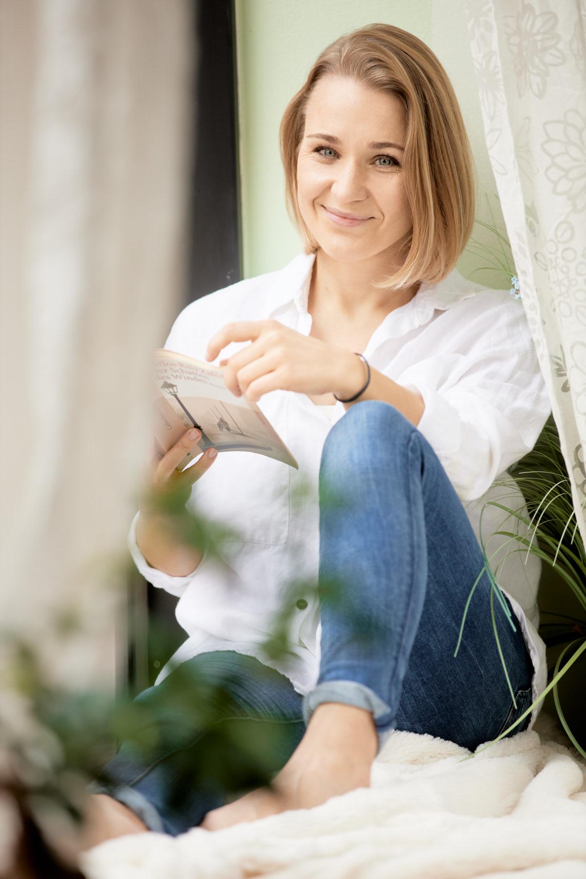 Dating-Foto einer jungen, blonden Frau, die gemütlich an eine Wand gelehnt ein Buch liest