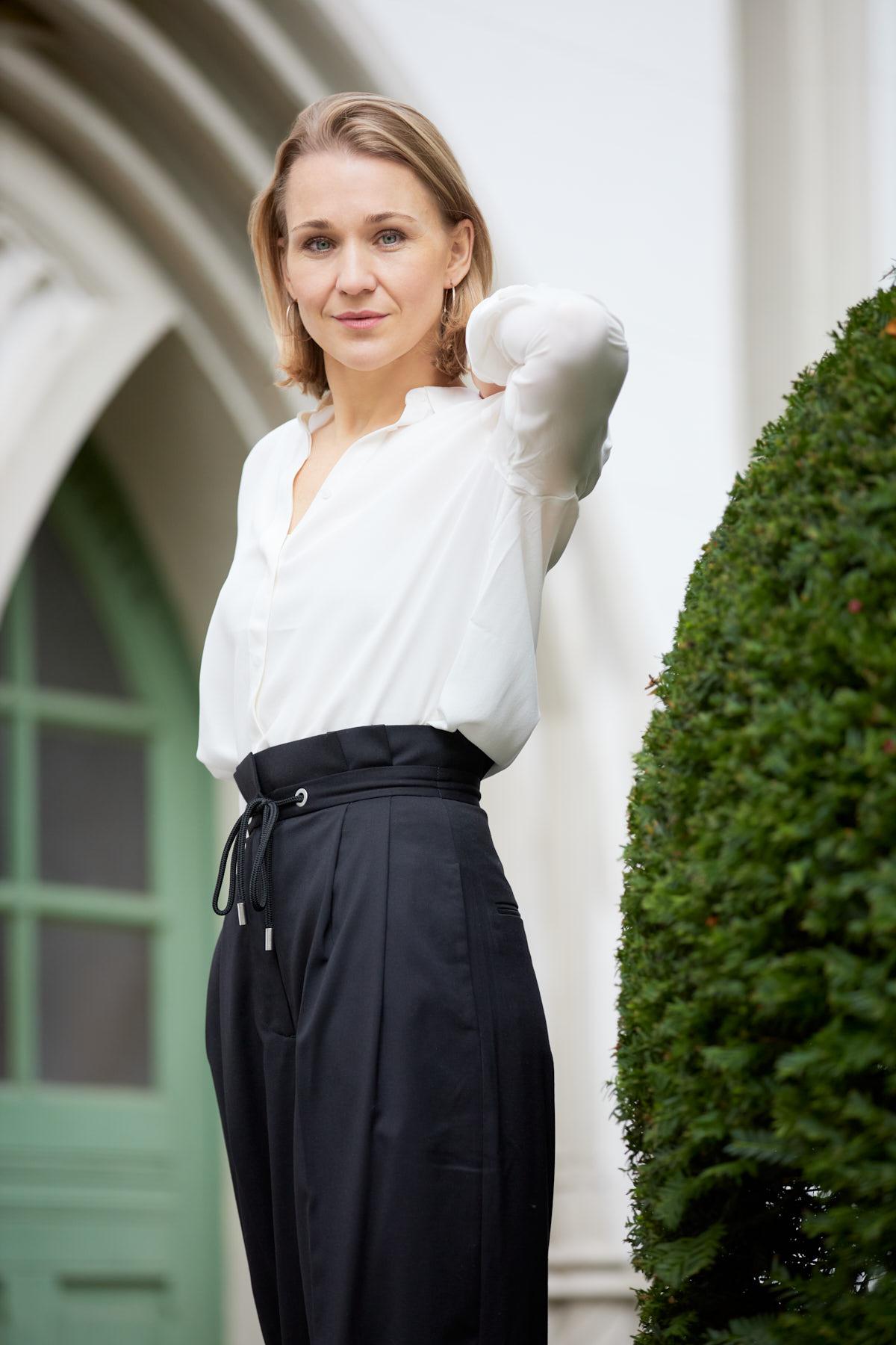 Dating-Foto einer elegant gekleideten jungen Frau , die neben einem grünen Busch vor eleganten Tür steht