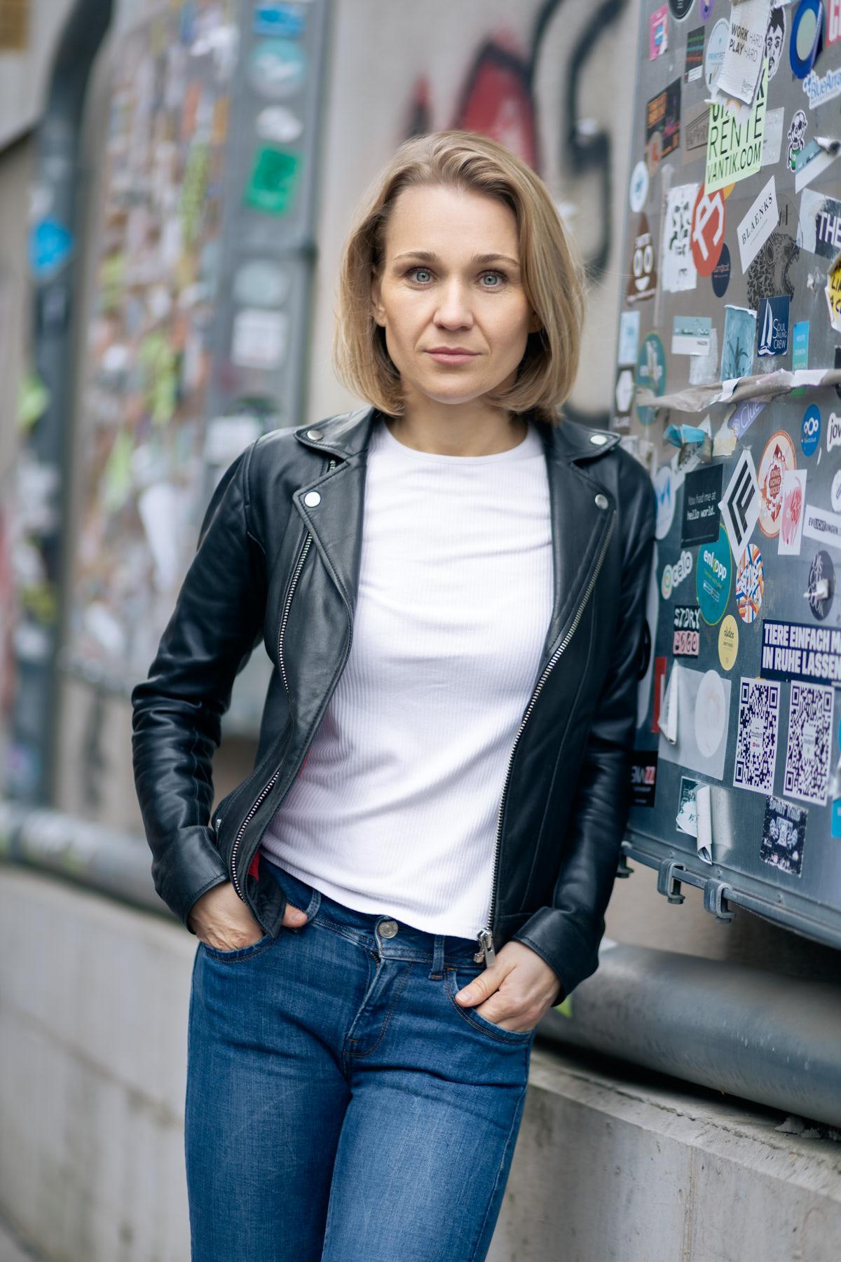 Dating-Foto einer jungen Frau mit blonden schulterlangen Haaren. Sie trägt eine Lederjacke und lehnt mit herausvorderndem Blick an einer Wand mit Aufklebern.