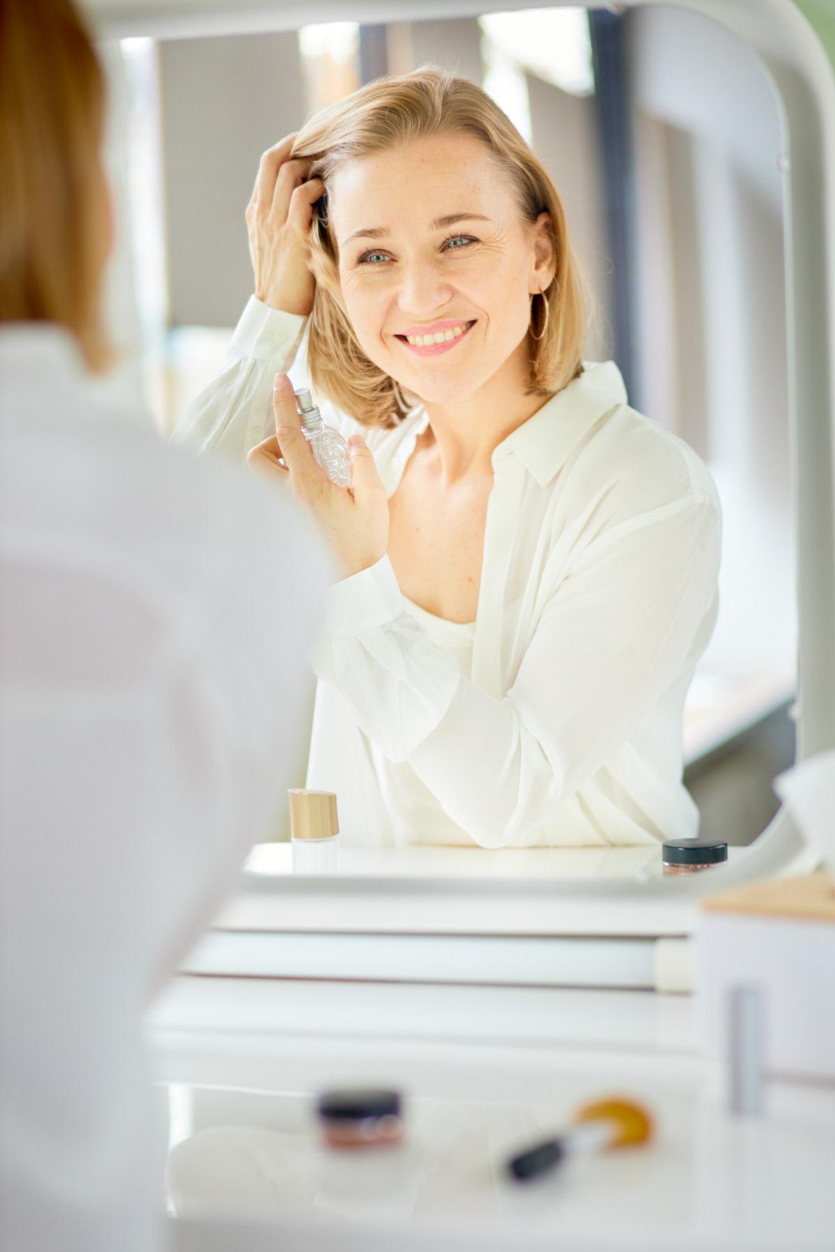 Dating-Foto einer jungen, blonden Frau in weißer Bluse, die sich vor einem Schminckspielgel mit Parfüm einsprüht