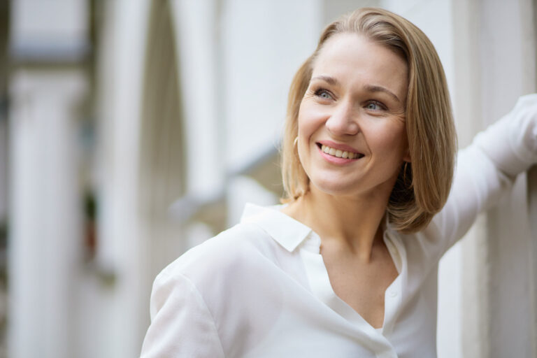 Schauspielerportraits einer jungen,lächelnden Schauspielerin die eine weiße Bluse trägt und vor einem hellen Hintergrund steht