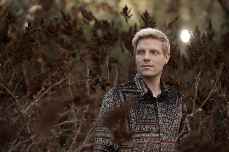 Schauspielerportraits eines jungen blonden Schauspielers der ein dunkel gemustertes Hemd trägt und zwischen braunen vertrockneten Blüten steht