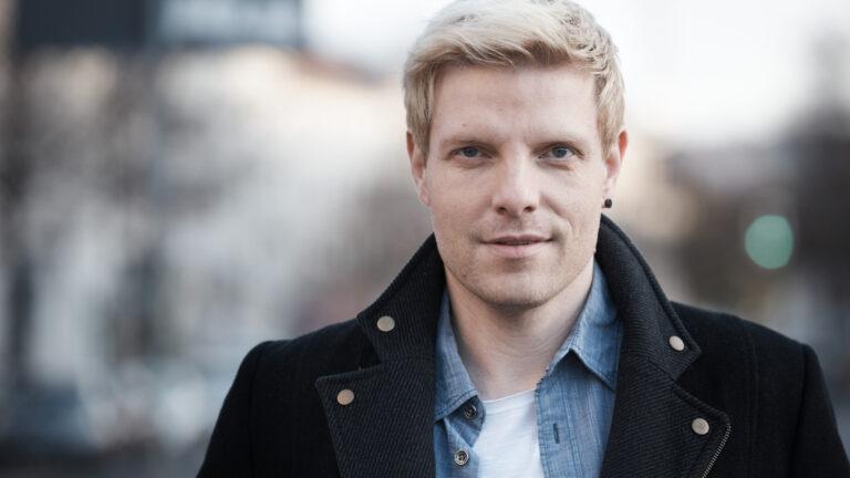 Schauspielerportraits eines jungen blonden Schauspielers in schwarzem Mantel mit hochgestelltem Kragen der ein wenig spöttisch direkt in die Kamera blickt