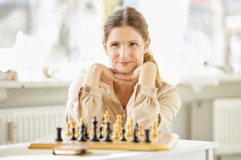 Schauspielerportraits einer Schauspielerin mit blonden langen Haaren. Sie trägt eine helle beige Bluse und sitzt mit auf den Händen aufgestütztem Kopf lächelnd vor einem Schachspiel