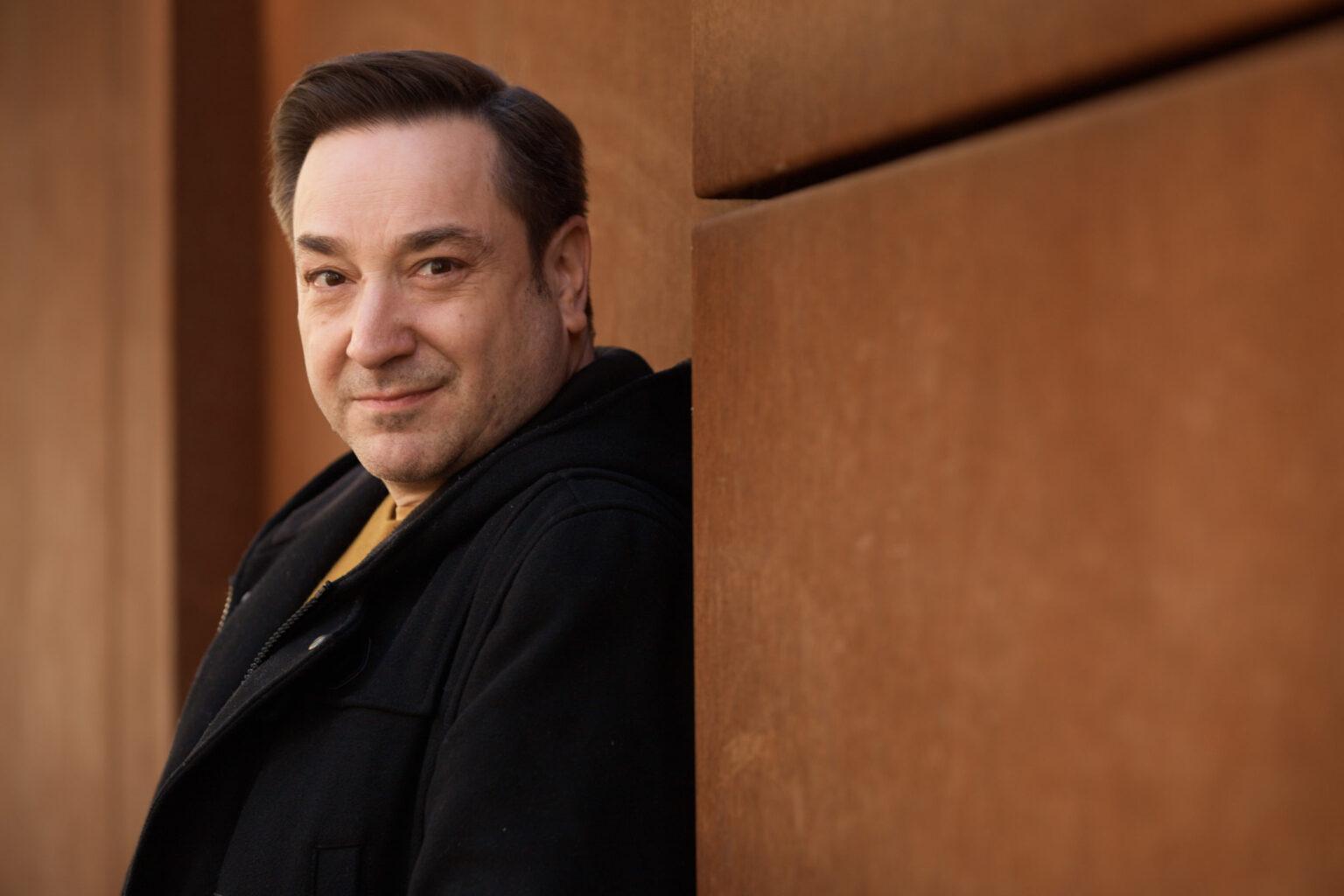 Schauspielerportraits eines dunkelhaarigen Schauspielers, der in einer schwarzen Jacke um eine rostige Stahlwand lächelt