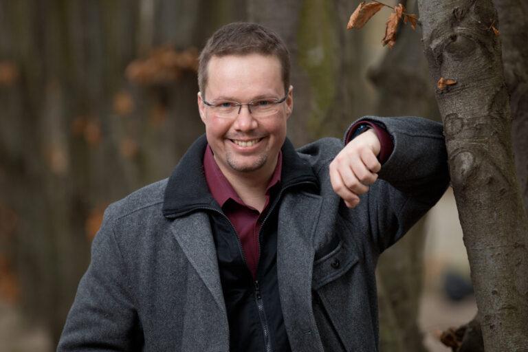 Schauspielerportraits eines dunkelhaarigen Schauspielers mit randloser Brille, der sich in einer grauen Jacke an einen Baum abstützt