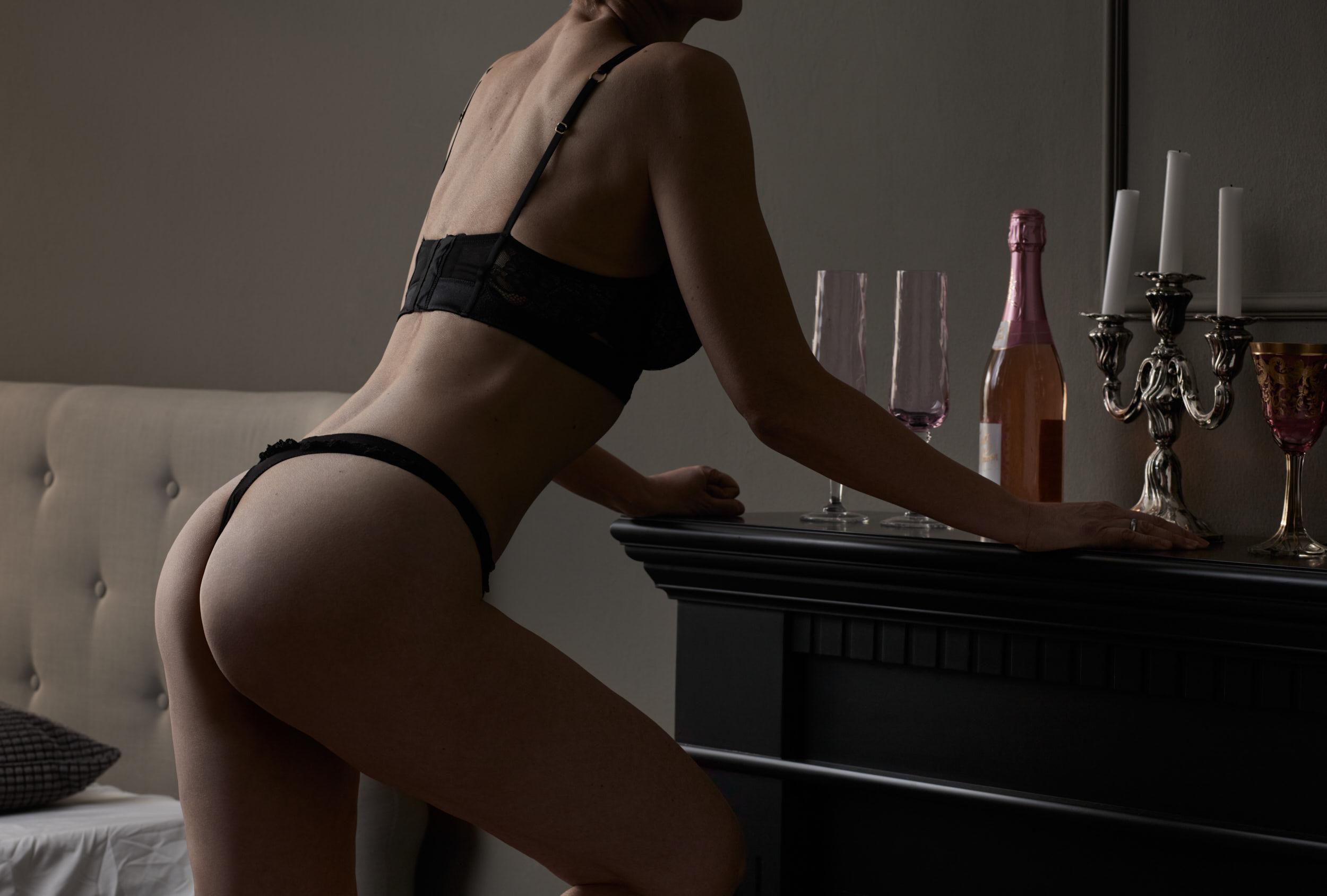 Akt-Fotoshooting einer erwachsenen Frau die in schwarzer Unterwäsche in einem Zimmer an einem Kamin lehnt, auf dem Sekt mit Gläsern und ein Kerzenleuchter stehen