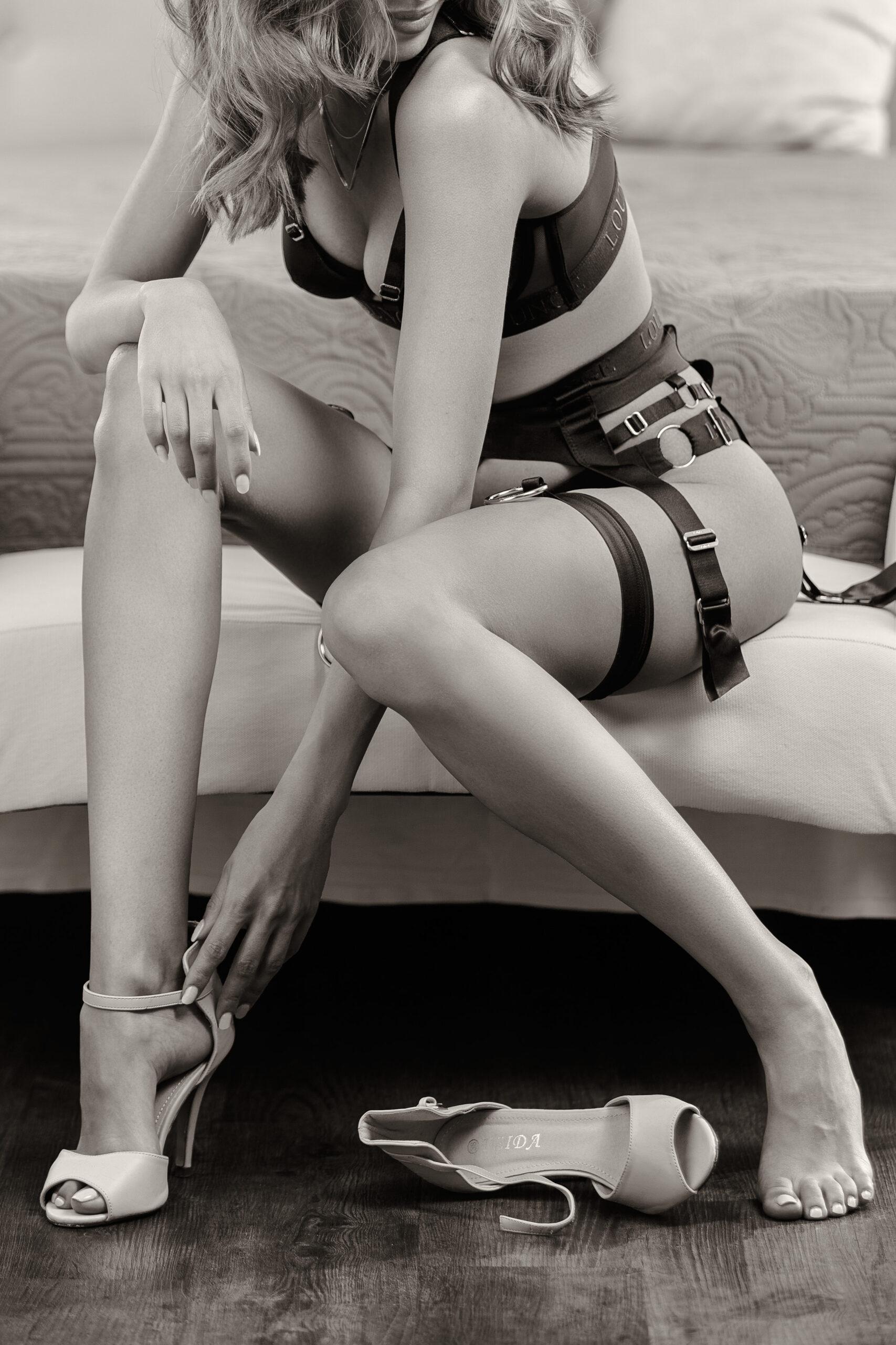 Boudoir-Fotoshooting einer rothaarigen Frau mit vollen Lippen die vor einem Bett auf einer Bank sitzt und ihre rosanen High Heels Schuhe anzieht.