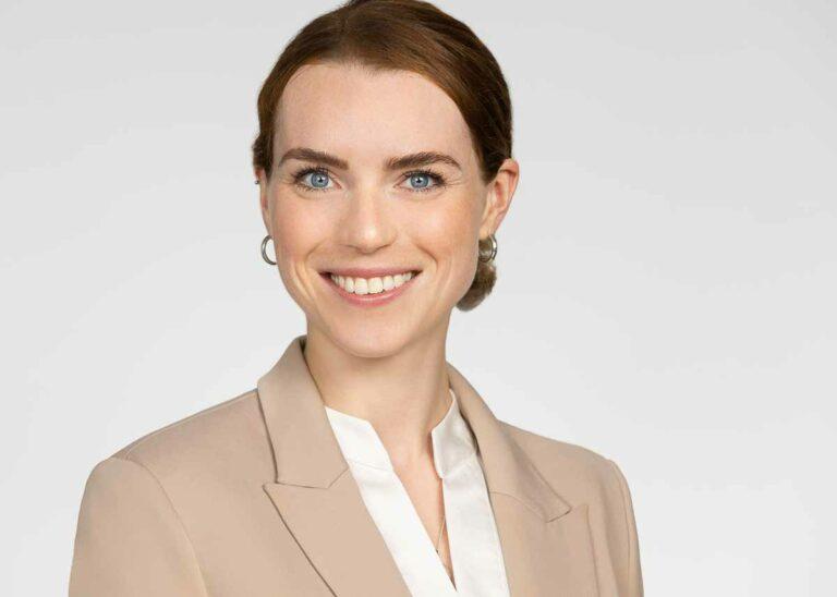 Modernes Bewerbungsfoto einer blauäugugen Frau mit braunen Haaren die zu einem Zopf geknotet sind und einen beigen Blaser trägt vor einem hellen Hintergrund.