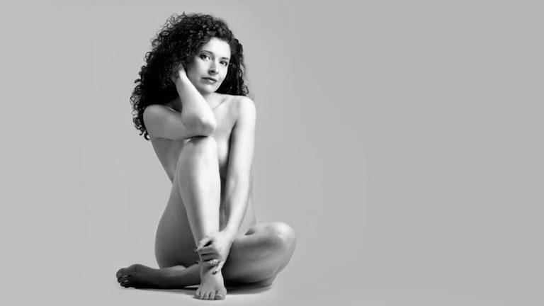 Schwarzweiss Aktfoto einer auf dem Boden sitzenden Frau mit lockigen Haaren