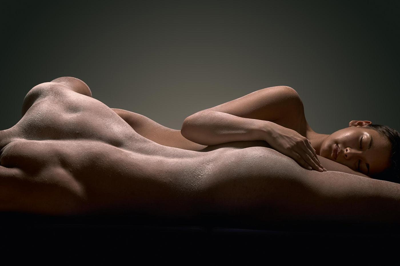 Aktfoto eines Paars. Muskulöser Mann liegt auf dem Bauch und junge Frau hat ihren Kopf auf seinen Oberschenkel gelegt und schläft.