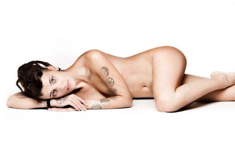 Aktfoto einer tätowierten Frau, die seitlich auf dem Boden liegt