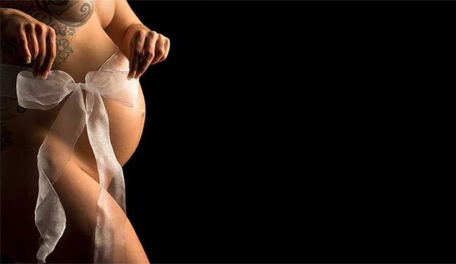 Foto einer Schwangeren Frau, die eine Schleife über ihrem Babybauch zurecht zieht