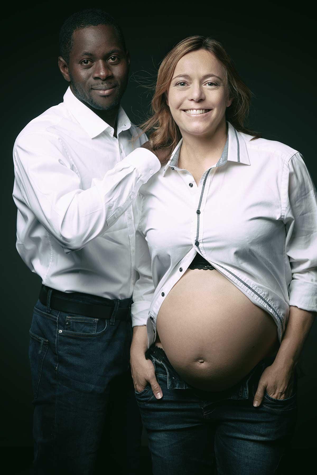 Dunkelhäutiger, werdender Vater und seine schwangere  Frau mit Babybauch haben weiße Hemden an und blicken direkt in die Kamera