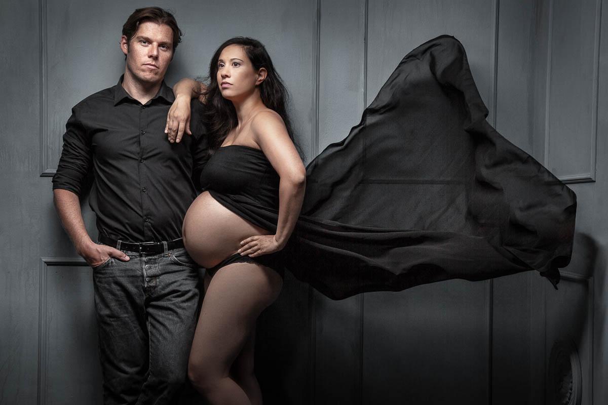 Cooles Babybauchfoto Paarfotoshooting einer schwangeren Frau zusammen mit dem werdenden Vater. Die Schangere stütz sich lässig auf die Schulter ihres Mannes, währen ein schwarzes Tuch hinter weht.