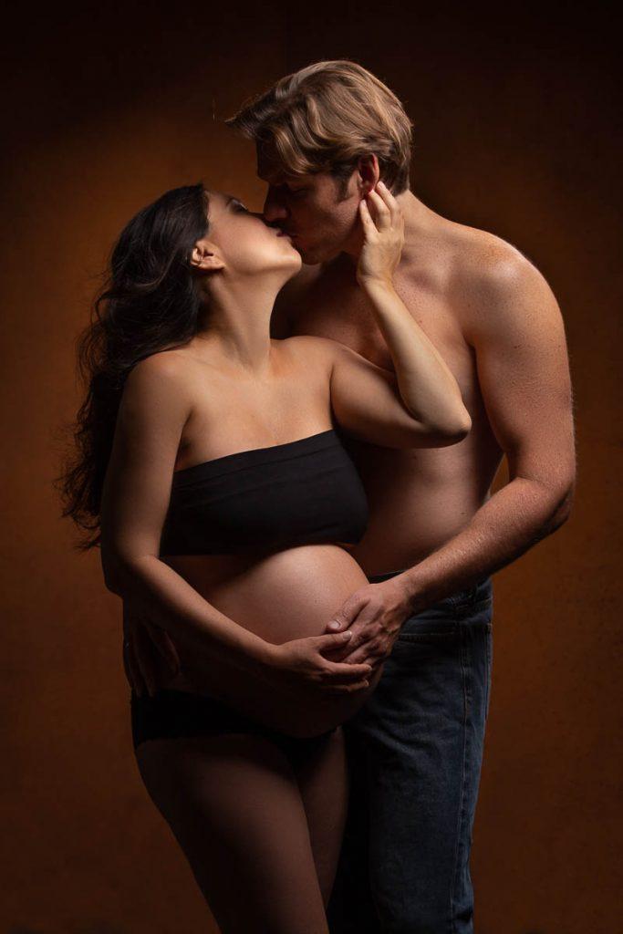 Schwangere Frau mit dickem Babybauch küßt Ihren Mann und berührt zart die Wange ihres Mannes