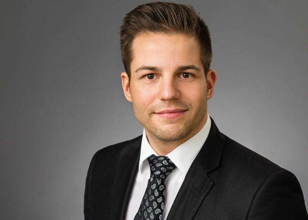 Bewerbungsfotos Berlin - Modernes Bewerbungsfoto eines Mannes mit Anzug und Krawatte mit Paisleymuster vor grauem Hintergrund vom Fotostudio Farbtonwerk in Berlin Mitte